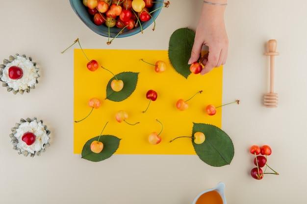 Вид сверху спелой дождливой вишни на листе желтой бумаги и творога в мини-пирожных банок на белом