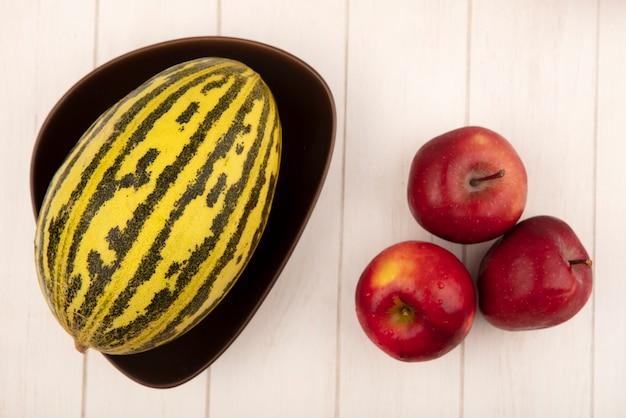 Вид сверху спелых красных яблок с дыней на миске на белой деревянной поверхности