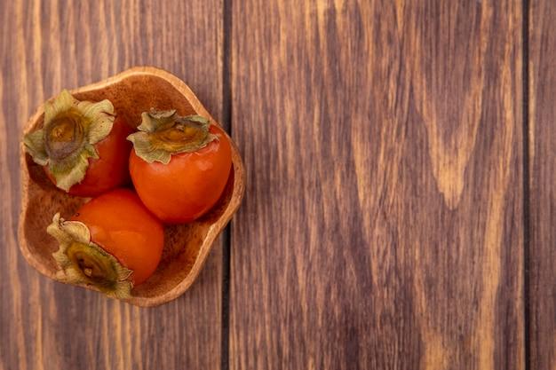 コピースペースのある木製の表面にある木製のボウルに熟した柔らかくてジューシーな柿の上面図