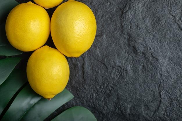 黒の背景に熟した黄色のレモンの上面図