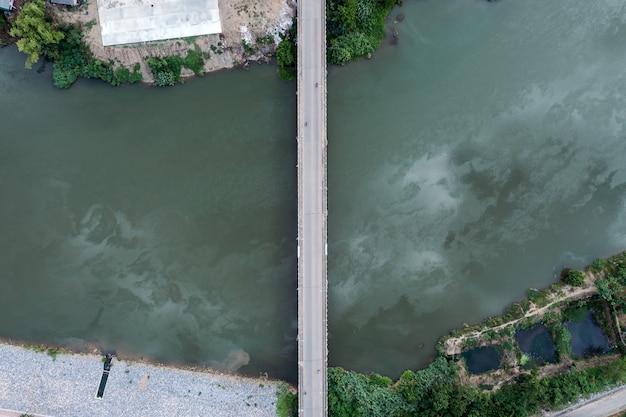 교외에서 물에 기름 얼룩이 있는 강 위에 있는 도로 다리의 상위 뷰