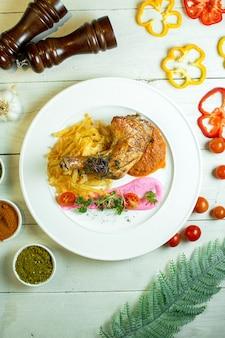 Вид сверху жареной куриной ножки с картофельными чипсами и баклажанной икрой на белой тарелке