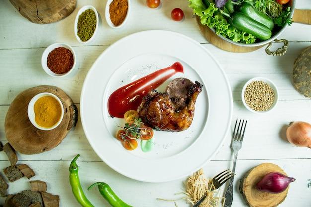 白い皿にチェリートマトとケチャップとローストチキンの脚のトップビュー