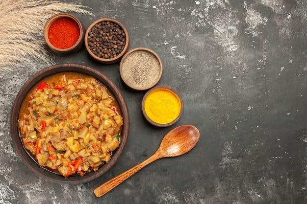 Вид сверху жареного салата из баклажанов в миске с разными специями в небольших мисках деревянной ложкой на темной поверхности