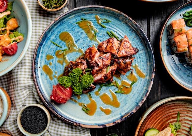 Вид сверху жареной курицы с жареными помидорами свежей зеленью и соусом на тарелке на дереве
