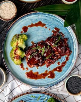 Вид сверху жареной курицы с кисло-сладким соусом и брокколи на тарелку на деревянной поверхности