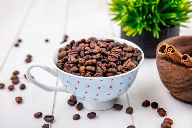 흰색 나무 배경에 나무 그릇에 계 피 스틱 컵에 볶은 커피 콩의 상위 뷰