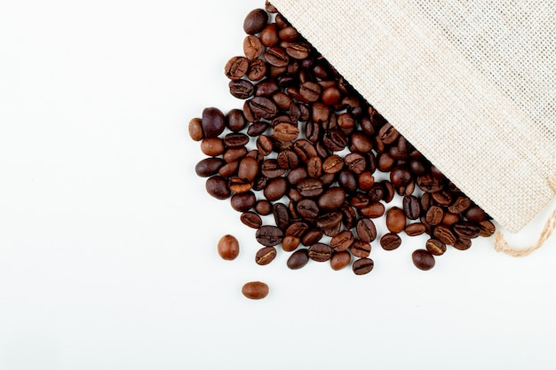 コピースペースと白い背景の袋から散らばってローストコーヒー豆のトップビュー