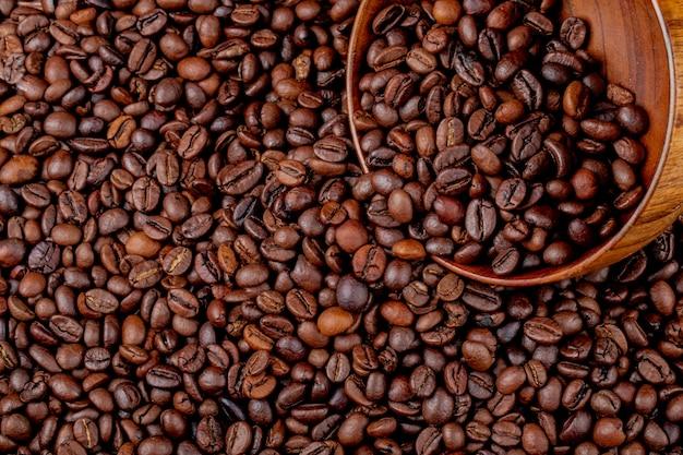 Вид сверху жареных кофейных зерен, разбросанных из деревянной миски на фоне кофейных зерен