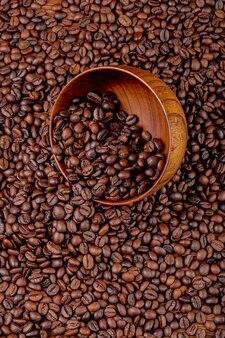 木製のボウルから散在しているローストコーヒー豆のトップビュー