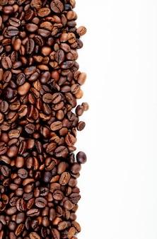 Вид сверху жареных кофейных зерен, разбросанных на белом фоне с копией пространства
