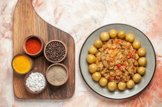 누드 표면에 커팅 보드에 향신료와 함께 접시 그릇에 구운 가지 샐러드와 절인 자두의 상위 뷰