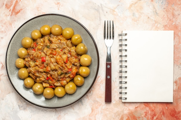 Вид сверху салата из жареных баклажанов и маринованных слив на тарелке, вилке, записной книжке на обнаженной поверхности