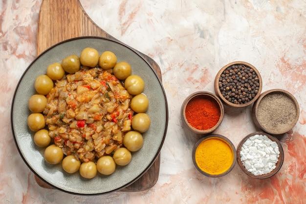 Вид сверху салата из жареных баклажанов и маринованных слив на тарелке на разделочной доске на обнаженной поверхности