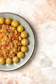 Вид сверху салата из жареных баклажанов и маринованных слив на тарелке на обнаженной поверхности