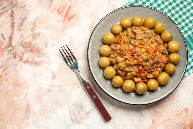 Вид сверху салата из жареных баклажанов и маринованных слив на тарелке на бирюзовой белой клетчатой вилке для салфеток на обнаженной поверхности