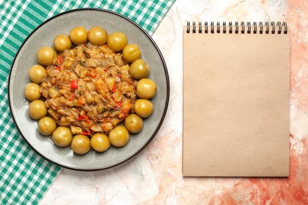 누드 표면에 청록색 흰색 체크 무늬 surface.cloth 메모장에 접시에 구운 가지 샐러드와 절인 자두의 상위 뷰