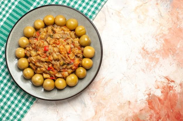 Вид сверху салата из жареных баклажанов и маринованных слив на тарелке на бирюзово-белой клетчатой поверхности