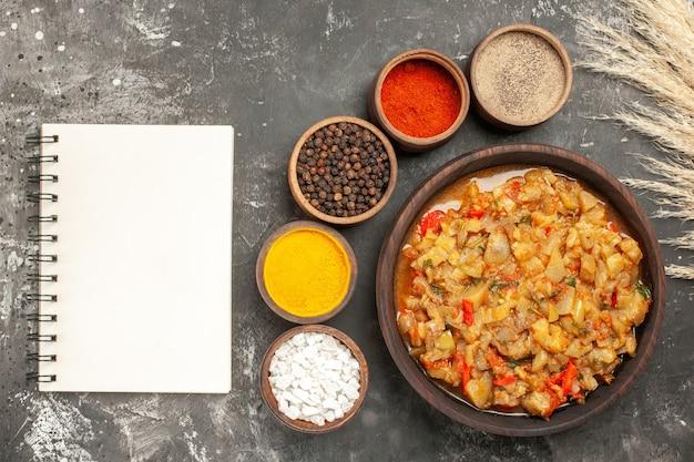 그릇에 구운 가지 샐러드와 작은 그릇에 다른 향신료의 상위 뷰 어두운 표면에 노트북