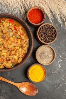 Вид сверху салата из жареных баклажанов в миске и различных специй в небольших мисках деревянной ложкой на темной поверхности