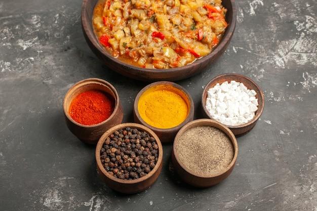 그릇에 구운 가지 샐러드와 어두운 표면에 작은 그릇에 다른 향신료의 상위 뷰