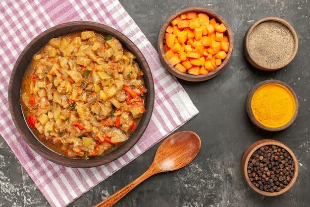Вид сверху салата из жареных баклажанов в мисках с разными специями нарезает детенышей моркови на темной поверхности