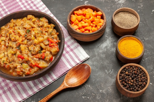 Вид сверху салата из жареных баклажанов в мисках с разными специями нарезает детенышей моркови деревянной ложкой на темной поверхности