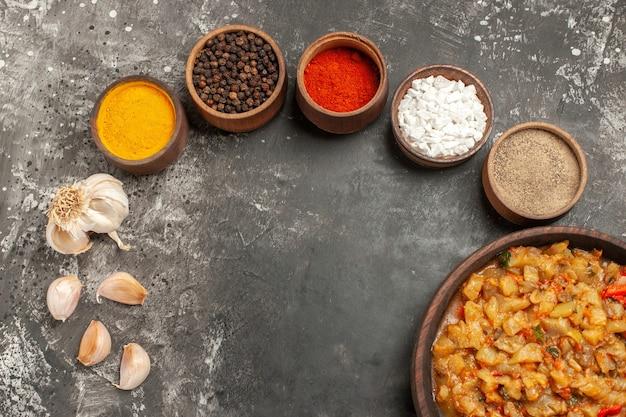어두운 표면에 그릇 마늘에 그릇 다른 향신료에 구운 가지 샐러드의 상위 뷰