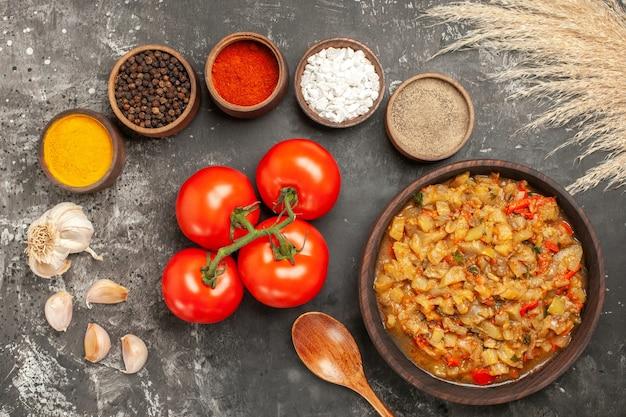 어두운 표면에 그릇 마늘 토마토에 그릇 다른 향신료에 구운 가지 샐러드의 상위 뷰