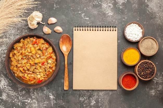 어두운 표면에 그릇 메모장에 그릇 기름 병 마늘 나무 숟가락 다른 향신료에 구운 가지 샐러드의 상위 뷰
