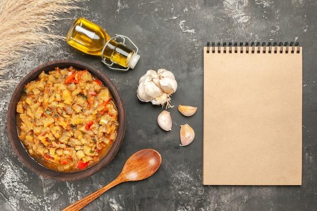 Вид сверху салата из жареных баклажанов в чашке с маслом, чесноком, деревянной ложкой, блокнотом на темной поверхности