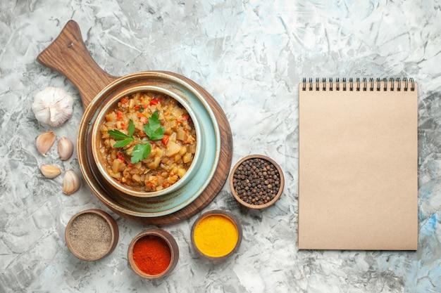まな板のボウルにローストナスサラダとボウルのさまざまなスパイスの上面図灰色の表面のノートブック 無料写真