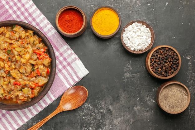 어두운 표면에 그릇에 그릇 나무 숟가락 다른 향신료에 구운 가지 샐러드의 상위 뷰