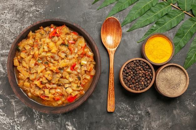 Вид сверху салата из жареных баклажанов в миске деревянной ложкой с разными специями в небольших мисках на темной поверхности