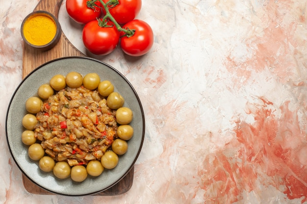 裸の表面のまな板トマトのプレート上のローストナスサラダの上面図