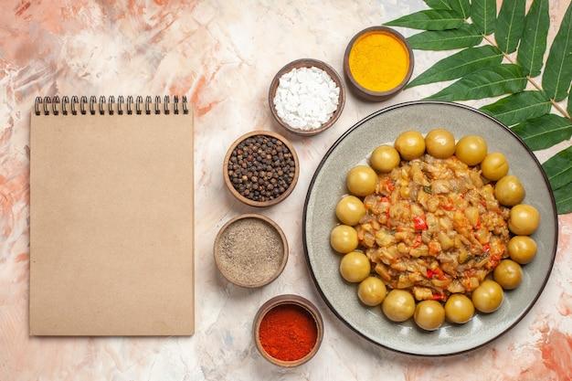 누드 표면에 작은 그릇 메모장에 접시 다른 향신료에 구운 가지 샐러드의 상위 뷰