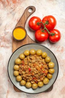 Вид сверху салата из жареных баклажанов на тарелке на разделочной доске, помидоры на обнаженной поверхности