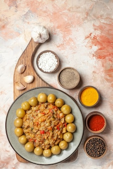 누드 표면에 그릇에 다른 향신료 도마에 접시에 구운 가지 샐러드의 상위 뷰