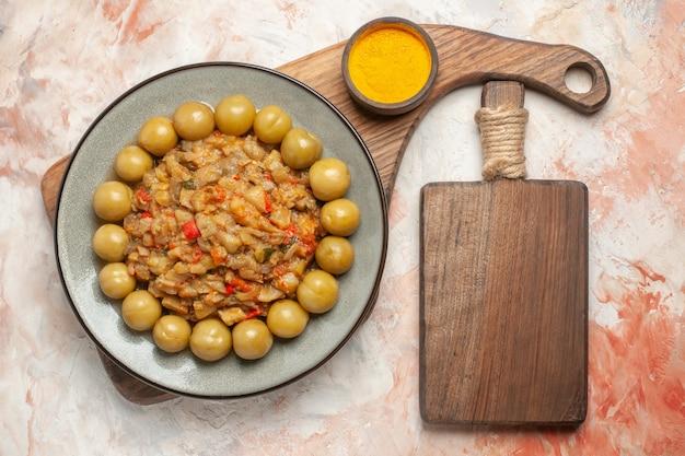 Вид сверху салата из жареных баклажанов на тарелке с куркумой в миске на деревянной сервировочной доске, разделочной доске на обнаженной поверхности