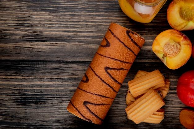 コピースペースを持つ素朴な木製のテーブルの上のガラスの瓶にクッキーとピーチジャムとロールケーキのトップビュー