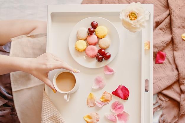 シルクのガウンの飲み物のバレンタインデーの女性のベッドの驚きのロマンチックな朝食の上面図...