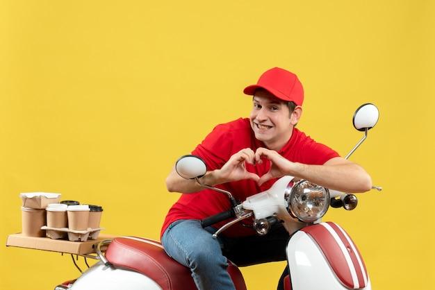 Вид сверху романтического молодого человека в красной блузке и шляпе, доставляющего заказы, делая жест сердца на желтом фоне