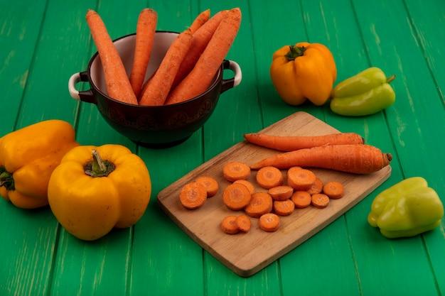Вид сверху корнеплодов моркови на миске с нарезанными ломтиками на деревянной кухонной доске с болгарским перцем, изолированным на зеленой деревянной стене