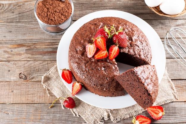나무 테이블에 딸기를 넣은 둥근 구운 초콜릿 스폰지 케이크의 꼭대기 전망. 복사 공간