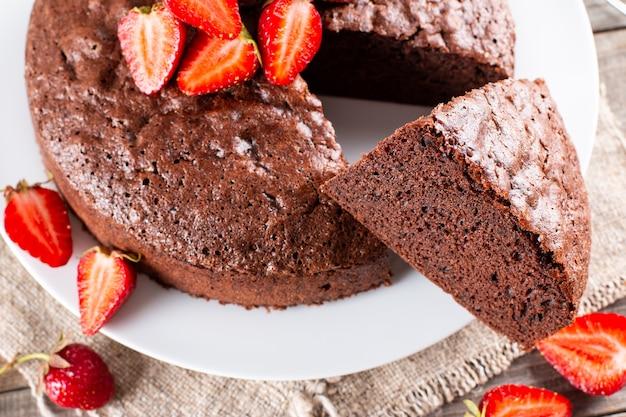 나무 테이블에 딸기를 넣은 둥근 구운 초콜릿 스폰지 케이크의 상위 뷰