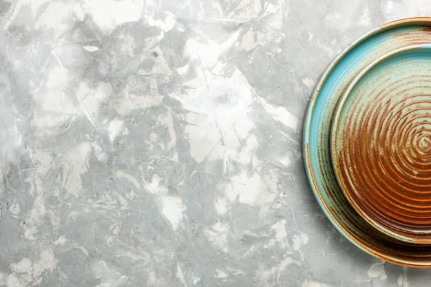 薄い灰色の表面で分離された空の丸い茶色の鍋の上面図