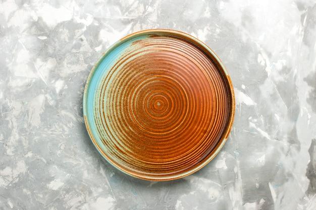Вид сверху круглой коричневой сковороды, пустой, изолированной на светло-серой поверхности
