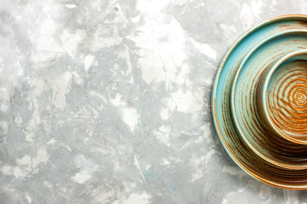 Вид сверху на круглые коричневые тарелки разного размера пустые, изолированные на светло-серой поверхности