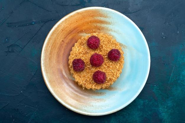 紺色の表面のプレート内に新鮮なラズベリーと丸いケーキの上面図