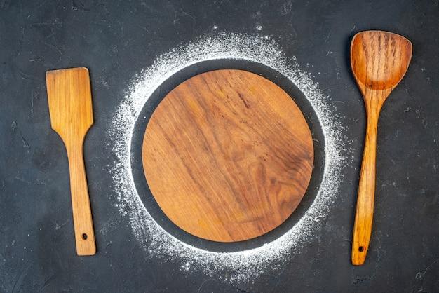 木のスプーンの周りに小麦粉と丸まな板の上面図